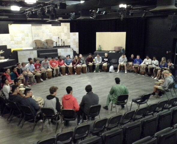 35+ Brophy HS students get a lesson in sabar drumming with Pape Diouf